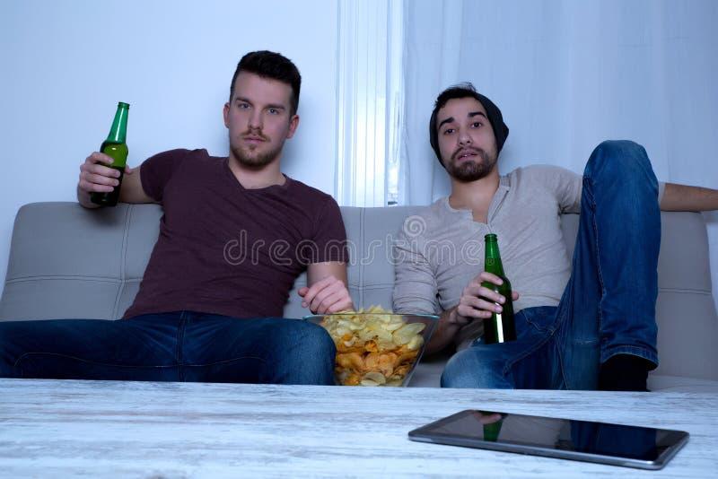 Zwei Freunde, die zu Hause fernsehen stockbilder