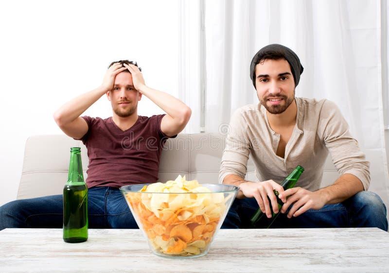 Zwei Freunde, die zu Hause fernsehen lizenzfreie stockbilder