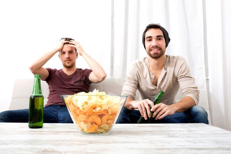 Zwei Freunde, die zu Hause fernsehen lizenzfreie stockfotos