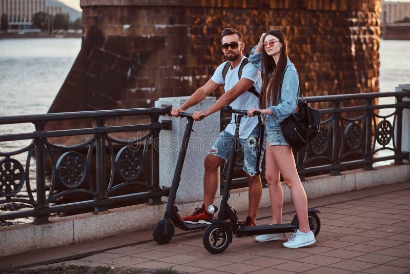 Zwei Freunde genießen Sommertag mit ihren Elektrorollern lizenzfreie stockbilder