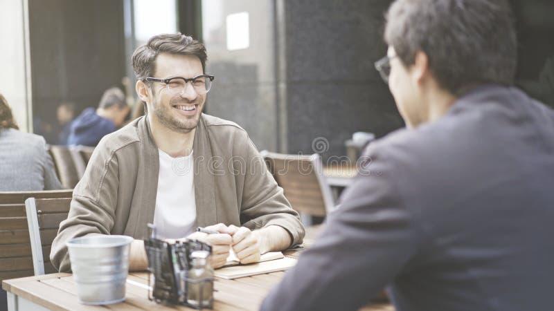 Zwei Freunde lachen bei Tisch vom Café draußen lizenzfreie stockbilder
