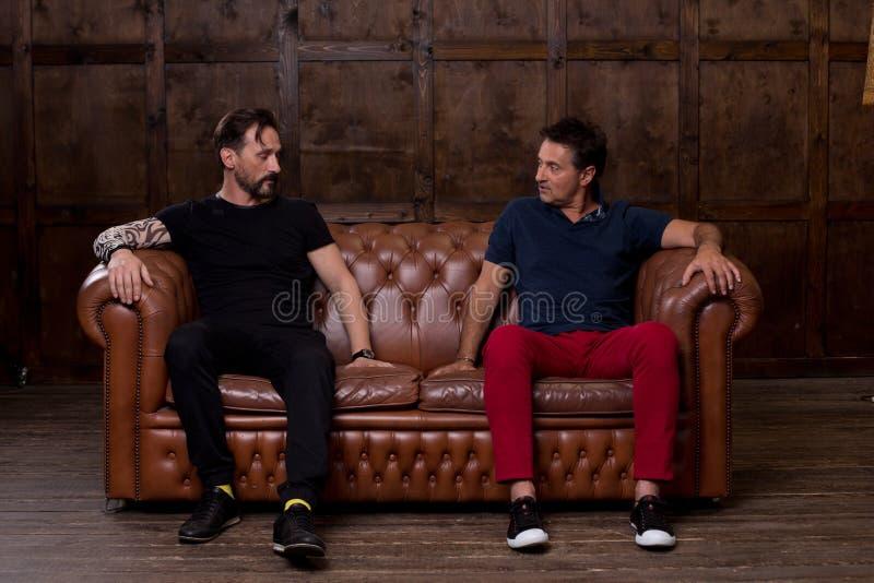 Zwei Freunde, welche die Sofaoberfläche berühren und sie besprechen lizenzfreies stockfoto