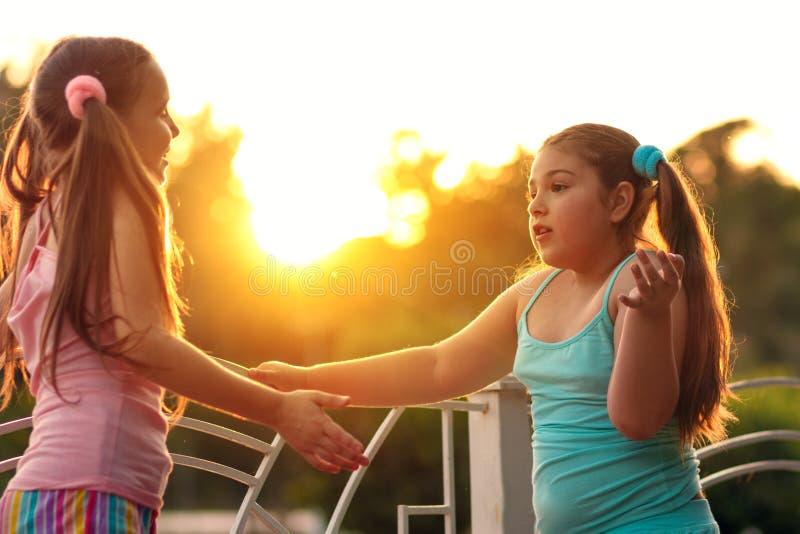 Zwei Freundinm?dchen, die auf der Stra?e bei Sonnenuntergang sprechen Schulm?dchen, zwei M?dchen im Urlaub stockbild