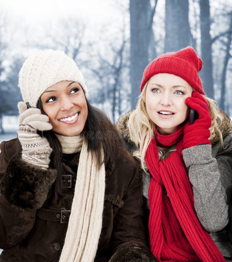 Zwei Freundinnen an den Telefonen draußen im Winter lizenzfreies stockbild