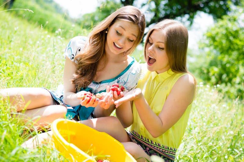 Zwei Freundinnen in der Freude Erdbeeren essend lizenzfreie stockfotografie