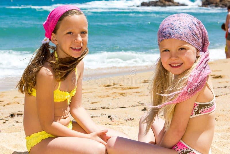 Zwei Freundinnen, die auf Strand sitzen. lizenzfreie stockbilder