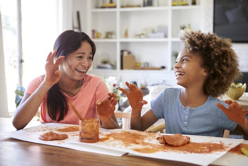 Zwei Freundinnen, die den Spaß spielt mit des Lehms zu Hause modellieren, ihre schmutzigen Hände miteinander lachen und zeigen, A lizenzfreie stockfotografie