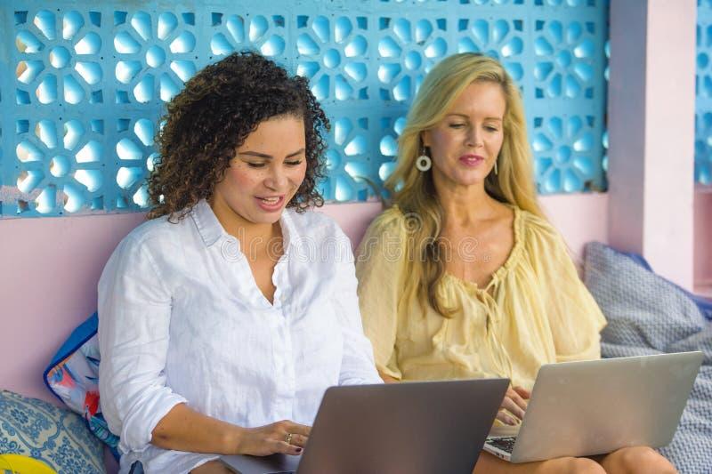 Zwei Freundinnen, die draußen am kühlen Café mit Laptop-Computer, ein Mädchenkaukasier, das andere Frauenafromisch zusammenarbeit lizenzfreie stockfotografie