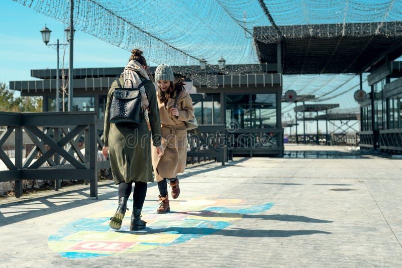 Zwei Freundinnen, die in einen Park gehen und Hopse auf der Pflasterung, Adoleszenz, Kindheit spielen lizenzfreies stockfoto