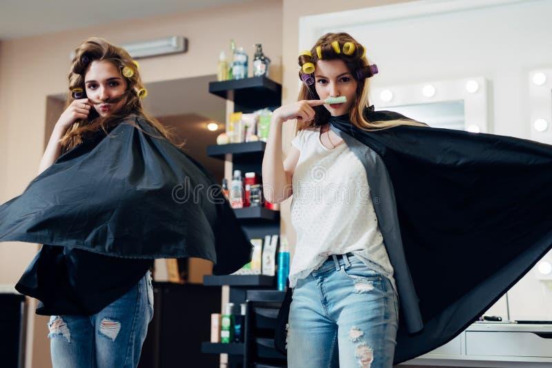 Zwei Freundinnen, die herum vor der Kamera herstellt Schnurrbart vom Haar und von Lockenwickler stehen im Fliegenkap vermasseln stockfotos