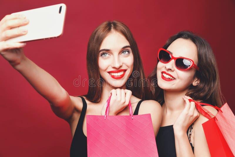 Zwei Freundinnen, die Papiereinkaufstaschen halten und Selfie machen stockfotografie