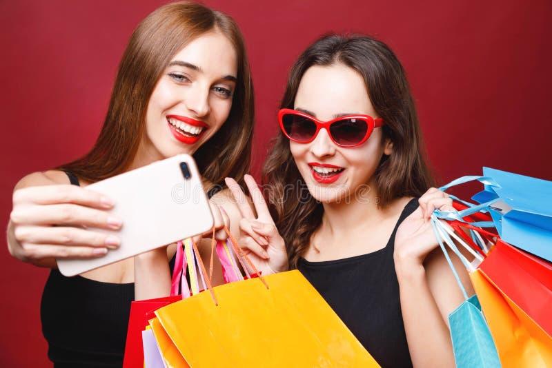 Zwei Freundinnen, die Papiereinkaufstaschen halten und Selfie machen stockfotos