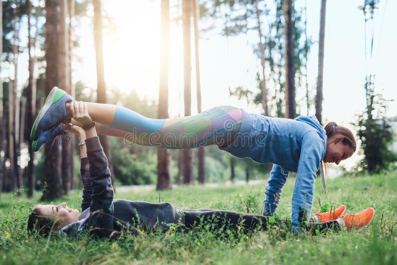 Zwei Freundinnen, die Partnerplanke tun, üben übenden pilates im Frühjahr Wald aus stockfotos
