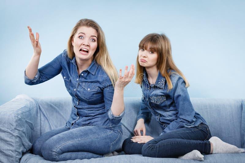 Zwei Freundinnen, die sonderbares Gespräch haben stockbild