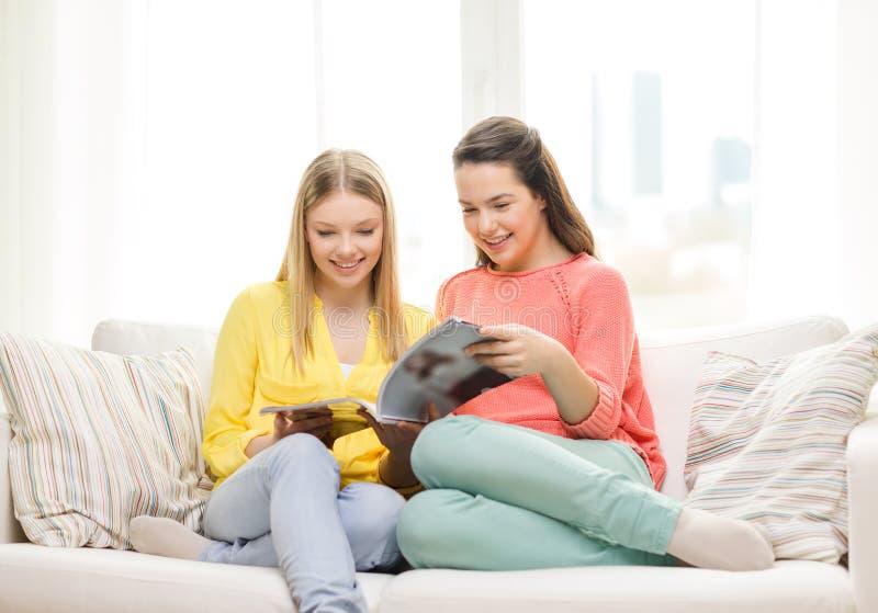 Zwei Freundinnen, die zu Hause Zeitschrift lesen lizenzfreie stockfotos