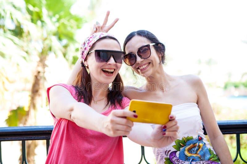 Zwei Freundinnen fotografierten sich am Telefon lizenzfreie stockfotos