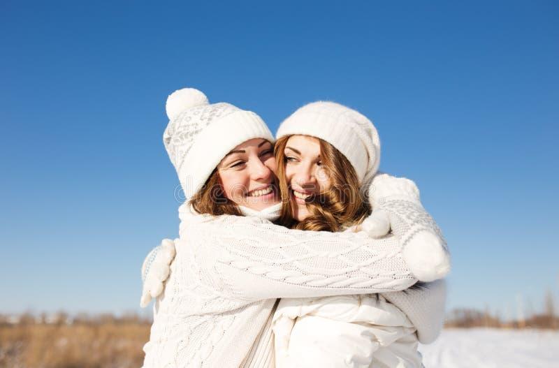 Zwei Freundinnen haben Spaß am Wintertag stockfotografie