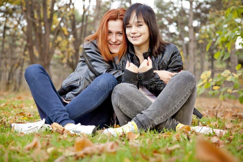 Zwei Freundinnen am Herbstpark. stockfotografie