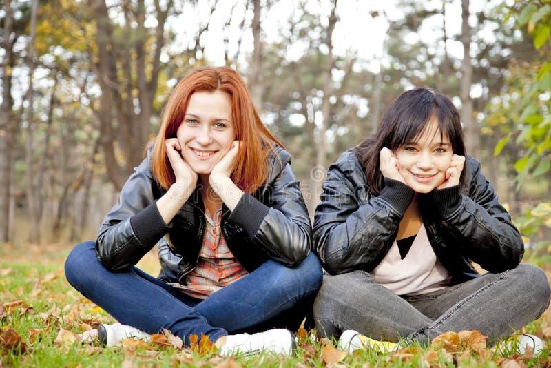 Zwei Freundinnen am Herbstpark. lizenzfreie stockfotos