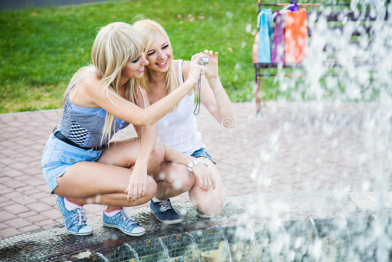 Zwei Freundinnen mit einer Fotokamera lizenzfreie stockfotografie