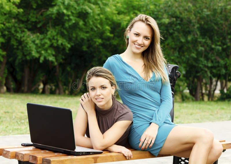 Zwei Freundinnen mit Laptop am Park lizenzfreies stockbild