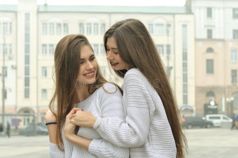 Zwei Freundinnen sind Händchenhalten und herum täuschen in der Stadt lizenzfreie stockfotos
