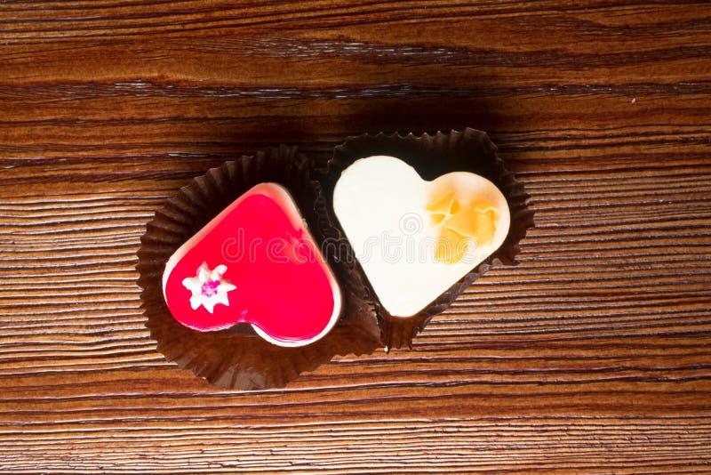 zwei frische Kuchen, rot und weiß, Herz formt auf hölzernen Hintergrund Köstliche Kuchen der Liebe lizenzfreies stockbild
