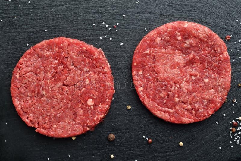 Zwei frische rohe schwarze Angus-Rindfleischburgerhauptpastetchen lizenzfreies stockfoto