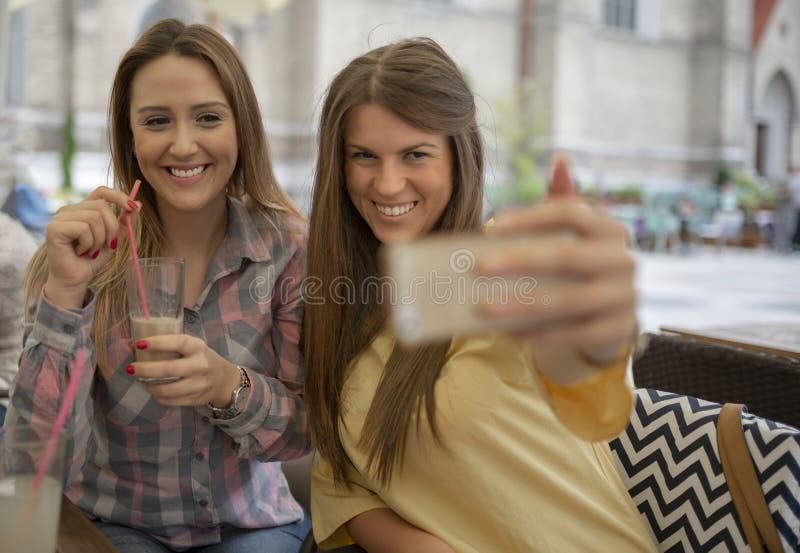 Zwei frohe nette Mädchen, die ein selfie beim Sitzen am Café nehmen stockbild