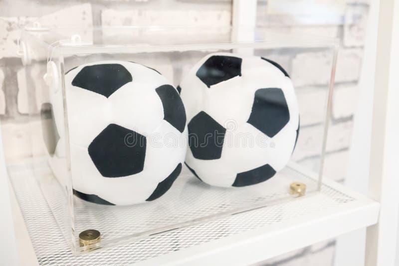 Zwei Fußballfußballkissen im klaren Acrylkasten für Anzeige lizenzfreie stockfotografie