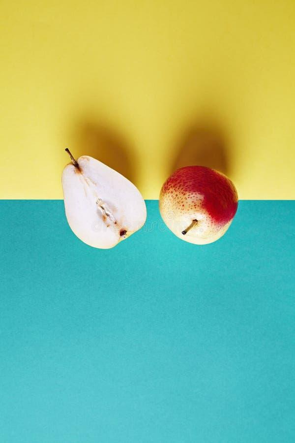 Zwei ganze frische Birne, Frucht schnitten in halbe Ansicht von oben genanntem auf grünem gelbem Hintergrund, modernes Artlebensm stockfoto