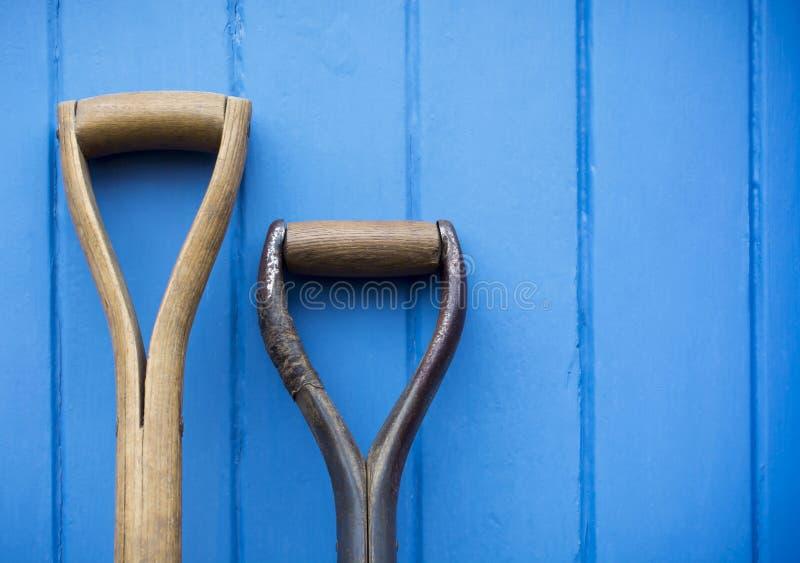Zwei Gartenwerkzeuggriffe gesützt gegen eine gemalte blaue Tür stockfoto