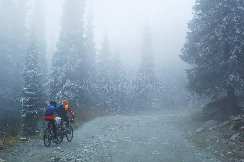 Zwei Gebirgsradfahrer im Nebel auf Berg stockfoto