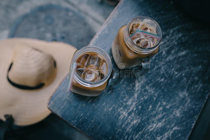 Zwei gefroren Kaffee im Sommer mit einem Latte auf einer Weinlesebank stockbild