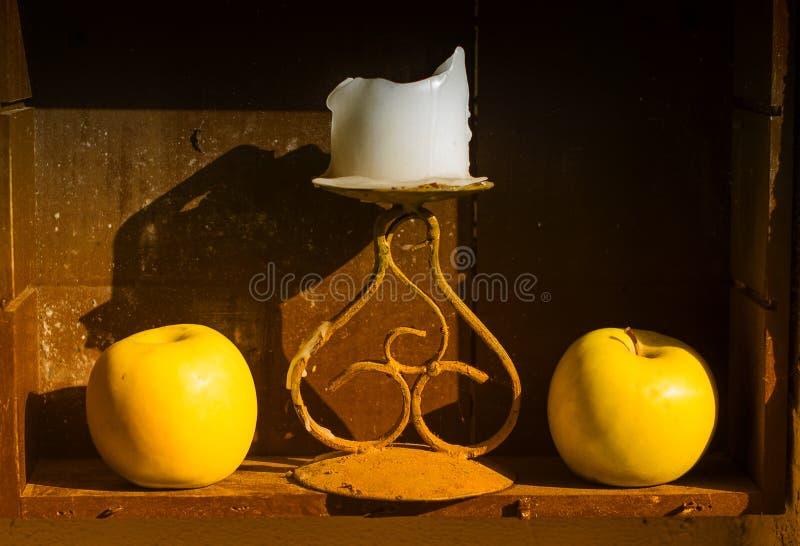 Zwei gelbe Äpfel und Kerze stockbild