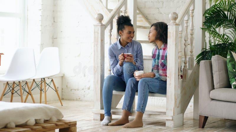 Zwei gelockte sistres Mädchen des Afroamerikaners, die auf Treppe sitzen, haben den Spaß, der zusammen lacht und zu Hause plauder stockbilder