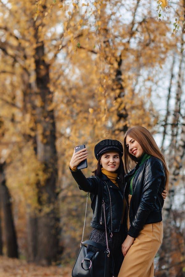 zwei gemütliche junge Mädchen gehen an der Herbstparkstraße Fotos machen stockfoto