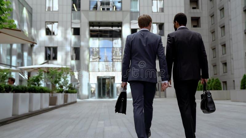 Zwei gemischtrassige Geschäftsmänner, die zum Bürogebäude, gegenseitige Arbeit besprechend gehen lizenzfreie stockfotos