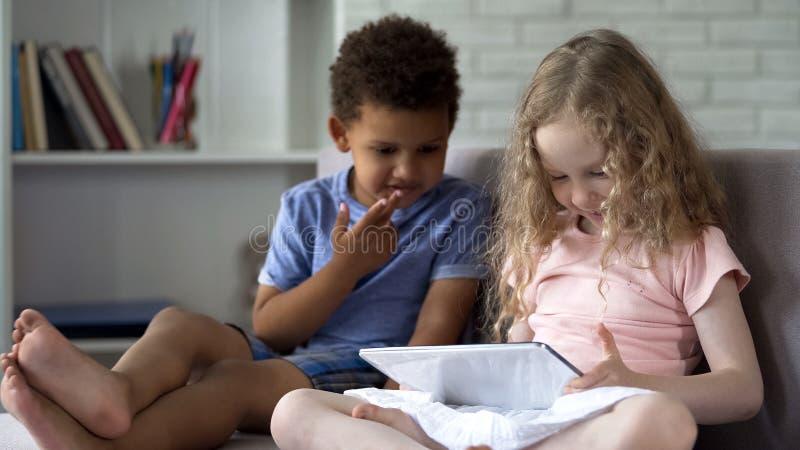 Zwei gemischtrassige Kinder, die auf gemütlichem Sofa und aufpassenden Karikaturen auf Tablette sitzen stockbilder