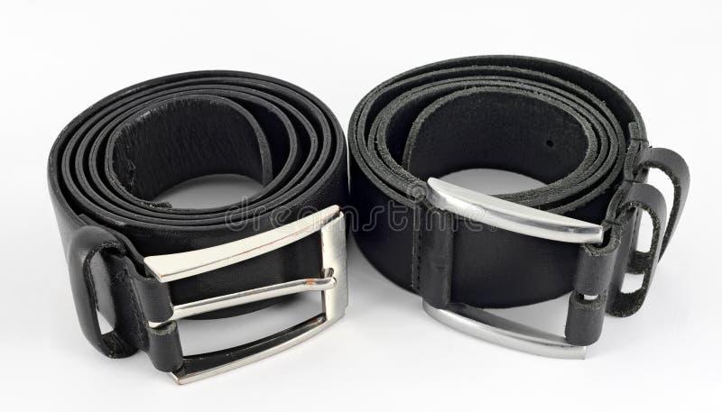 Zwei gerollt herauf Ledergürtel mit metallischen Schnallen lizenzfreies stockbild