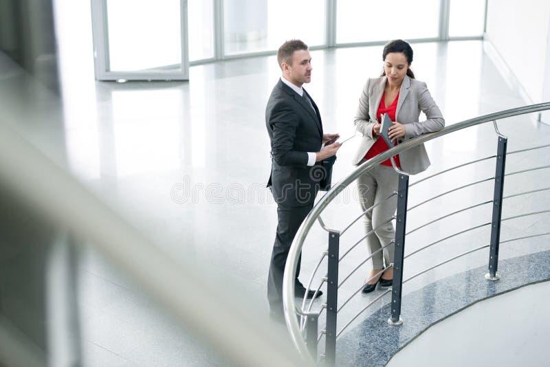 Zwei Geschäfts-Kollegen, die am Balkon sprechen lizenzfreies stockfoto