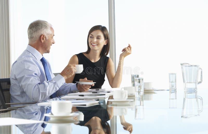 Zwei Geschäfts-Kollegen, die um die Sitzungssaal-Tabelle herein hat sitzen stockfotos
