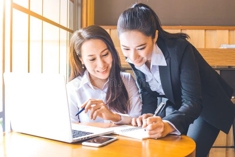 Zwei Geschäftsfrauen arbeiten an einem Notebook und halten a stockfotos