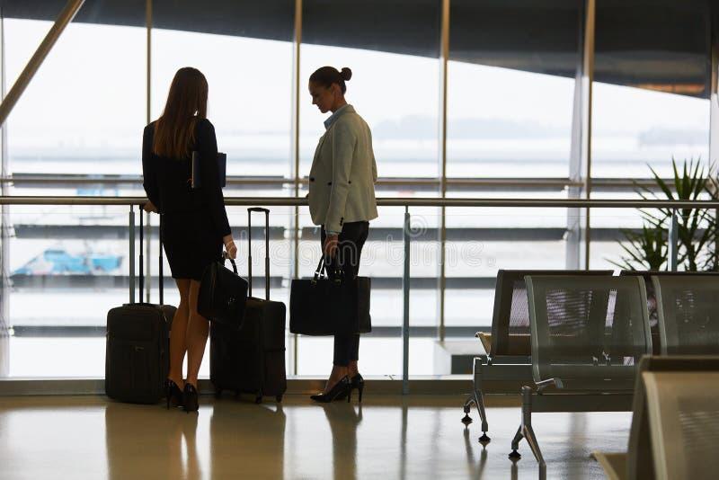 Zwei Geschäftsfrauen auf Geschäftsreise im Flughafen stockfotografie