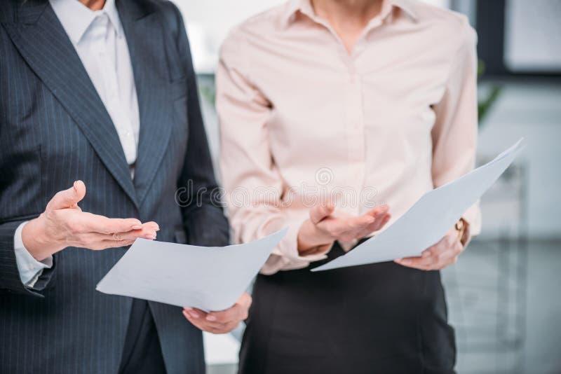 Zwei Geschäftsfrauen in der formellen Kleidung, die Papiere hält stockbild