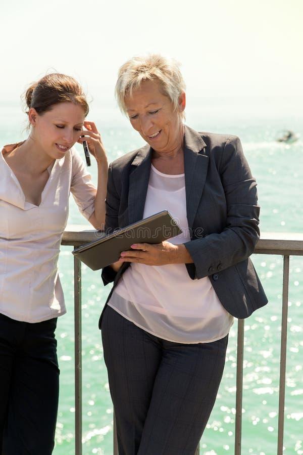 Zwei Geschäftsfrauen, die außerhalb des Büros arbeiten stockbilder