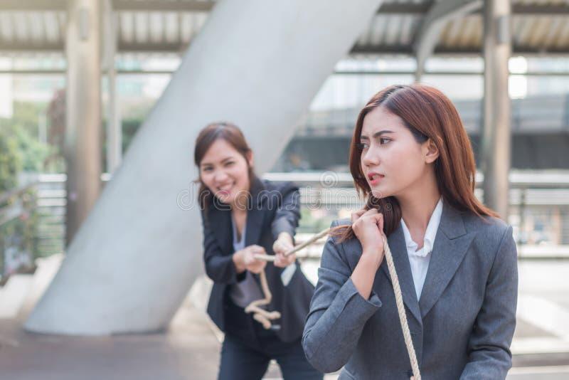 Zwei Geschäftsfrauen, die ein Seil im Wettbewerb mit der Verpflichtung zum Winzer ziehen stockfotografie