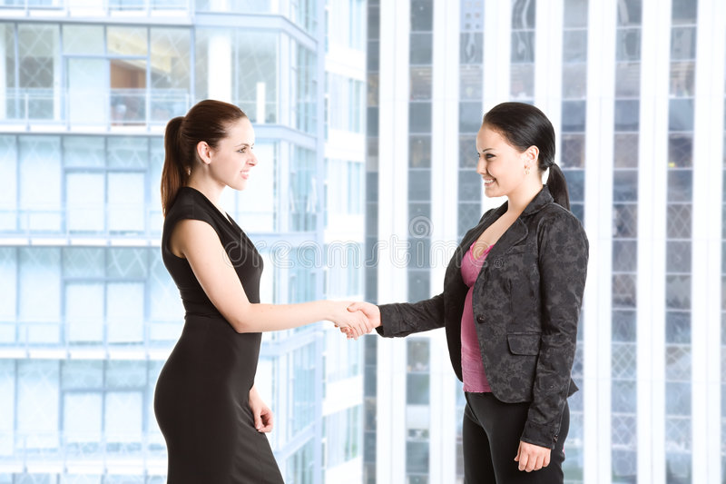 Zwei Geschäftsfrauen, die Hände rütteln stockbilder