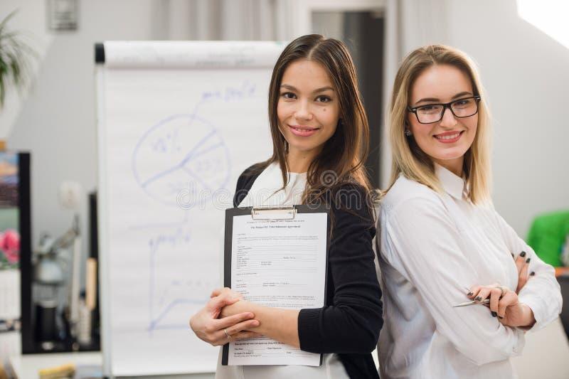 Zwei Geschäftsfrauen, die im Büro vor Flip-Chart stehen stockbild