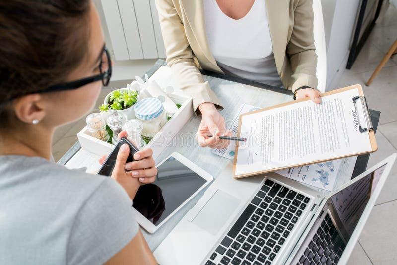 Zwei Geschäftsfrauen, die Vertrag besprechen lizenzfreies stockfoto
